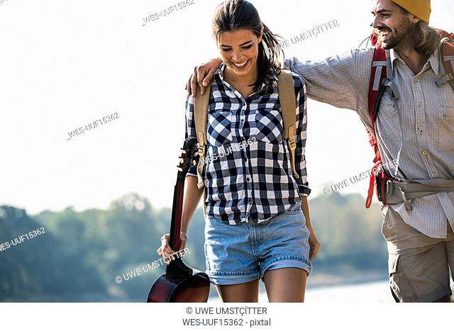 Happy young couple with backpacks and guitar outdoors