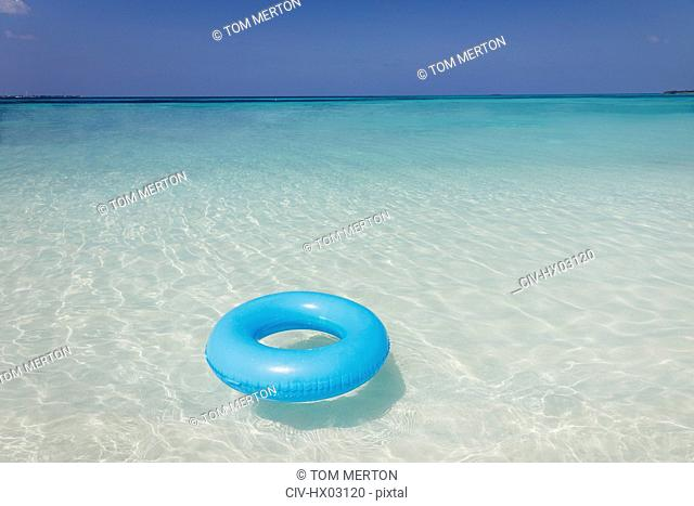 Blue inflatable ring floating in tropical ocean