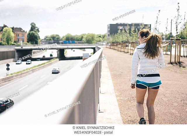 Sportive young woman walking beside motorway