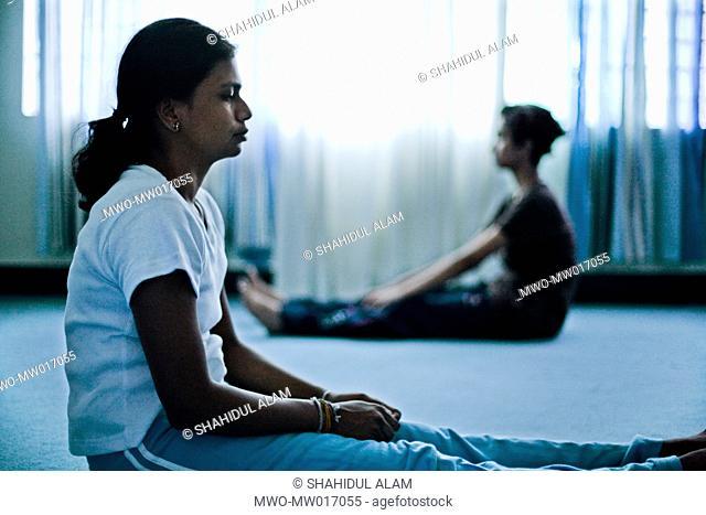 Mahilini Kailaiyangiri teaches her friends yoga in her dorm at the Asian University for Women Chittagong, Bangladesh July 2008