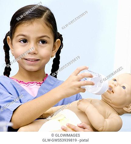 Close-up of a girl feeding a doll from a baby bottle