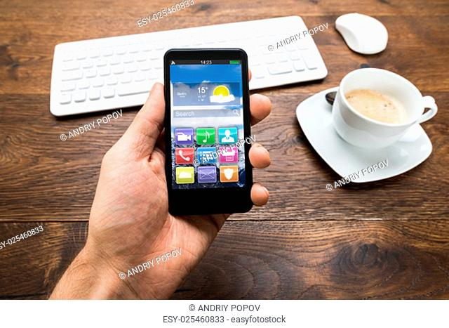 Close-up Of Person Hand Holding Mobile Phone With Apps And Cup Of Tea On Desk