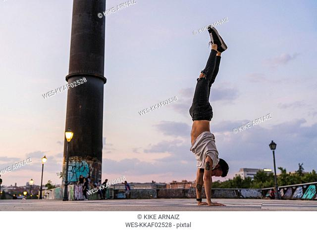 Young man doing a handstand in the city at sunset