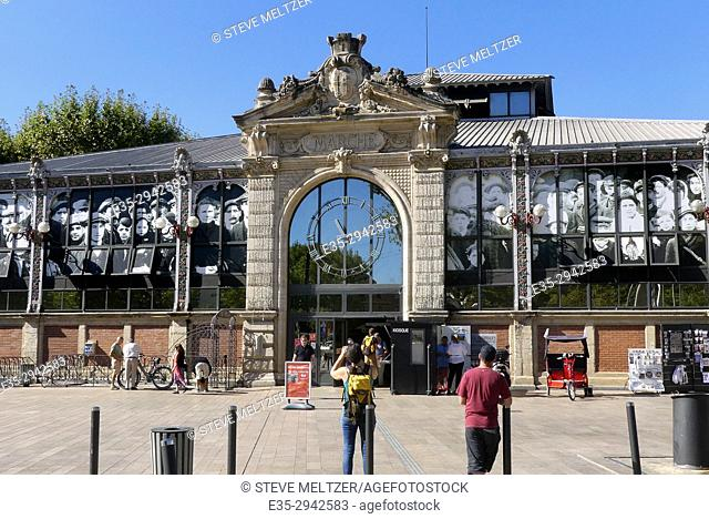 """A person takes a photo of """"""""Les Halles"""""""" market in Narbonne France that built in 1907"""