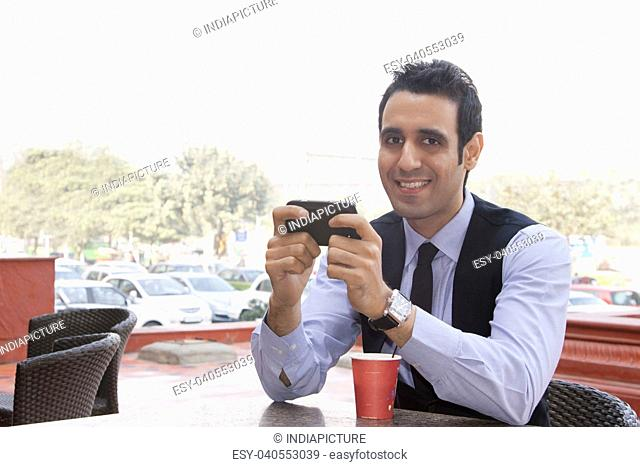 Portrait of a businessman with a mobile phone , INDIA , DELHI
