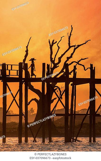 Silhouettes at U Bein teak bridge. local people and tourists enjoying sunset at Amarapura. Myanmar (Burma) travel landscapes and destinations