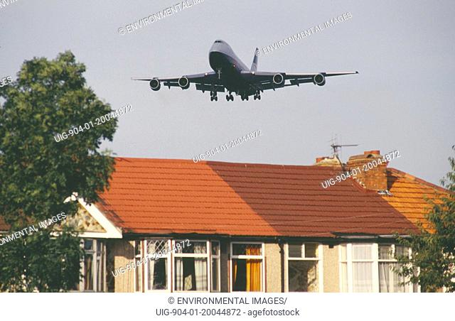 ENGLAND London Heathrow. Boeing 747 jumbo jet long haul airliner of British Airways low in flight over rooftops of residential area.