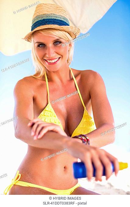 Woman applying sunscreen on beach
