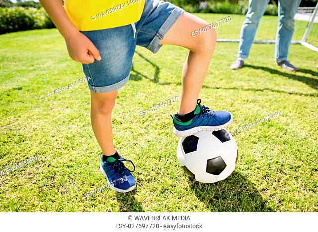 Low section of boy with leg on football