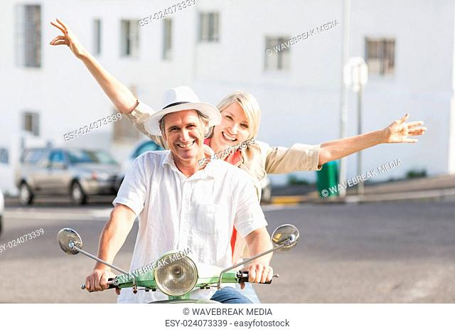 Happy couple riding motor scooter