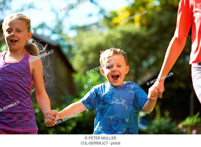 Siblings holding hands running in garden