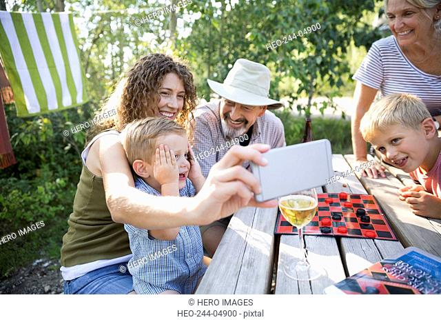 Multi-generation family taking selfie campsite picnic table