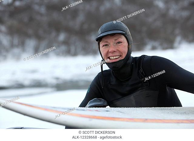 Portrait of a female surfer with surfboard, South-central Alaska; Homer, Alaska, United States of America