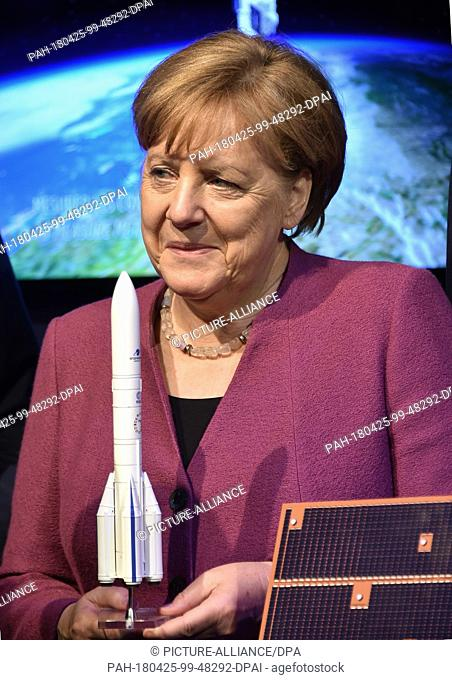 dpatop - 25 April 2018, Schönefeld, Germany: ..Chancellor Angela Merkel of the Christian Democratic Union is holding a model of the Ariane research rocket at...