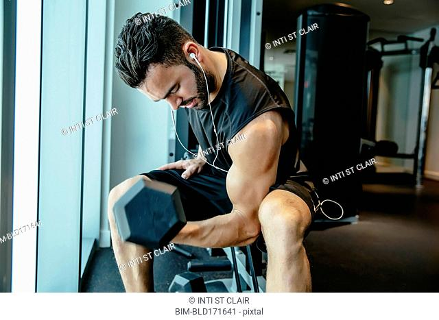 Man lifting weights in gymnasium