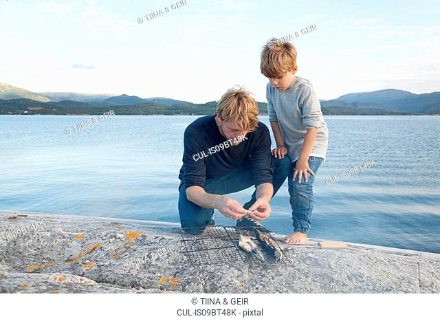 Boy and father preparing fish to grill on inlet rock, Aure, More og Romsdal, Norway