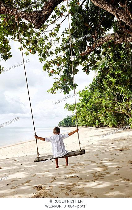 Thailand, Ko Yao Noi, boy on a swing on the beach