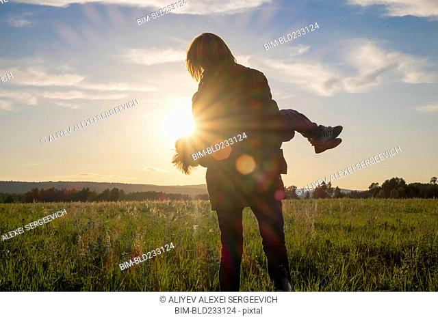 Woman carrying son in field at sunset