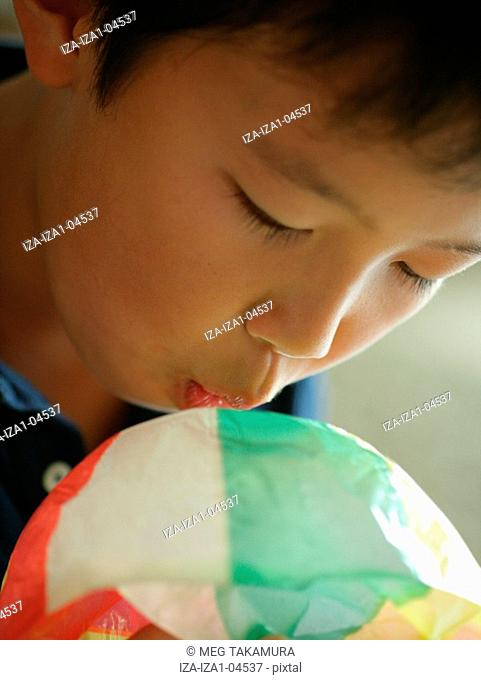 Close-up of a boy blowing a paper balloon