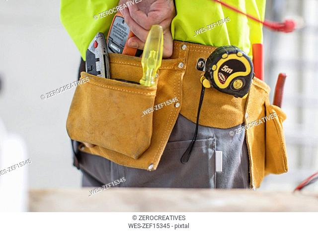 Close-up of construction worker with tool belt
