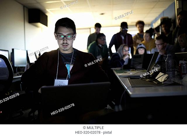 Focused male hacker working hackathon at laptop in dark office