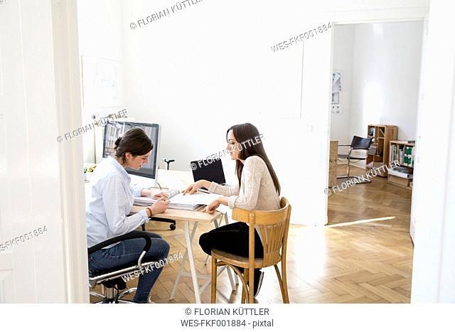 Two women discussing documents in office