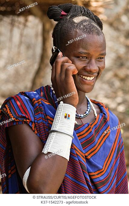 Maasai man wearing traditional dress and using modern smart phone