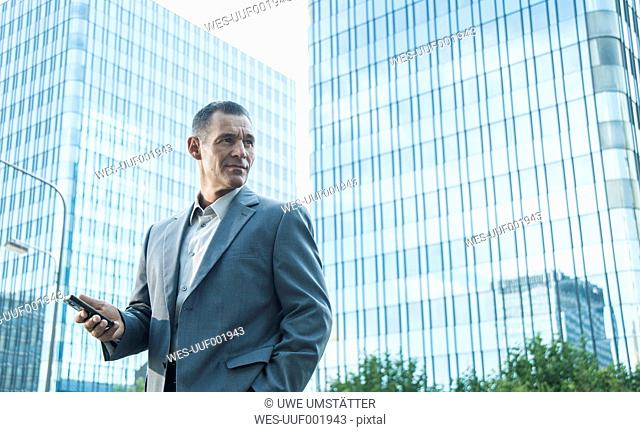 Mature businessmanwith cell phone outside office building