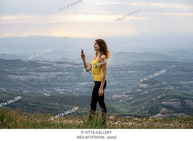 Spain, Barcelona, young woman taking selfie on Montcau Mountain