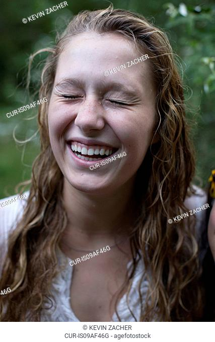 Woman laughing with eyes closed