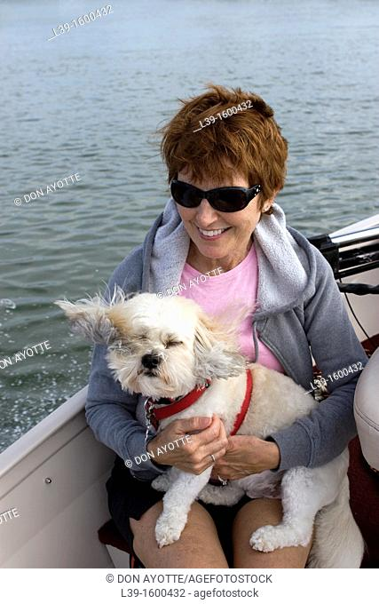 Woman and her dog riding in a boat on the Intracoastal waterway in Crescent Beach, FL, USA