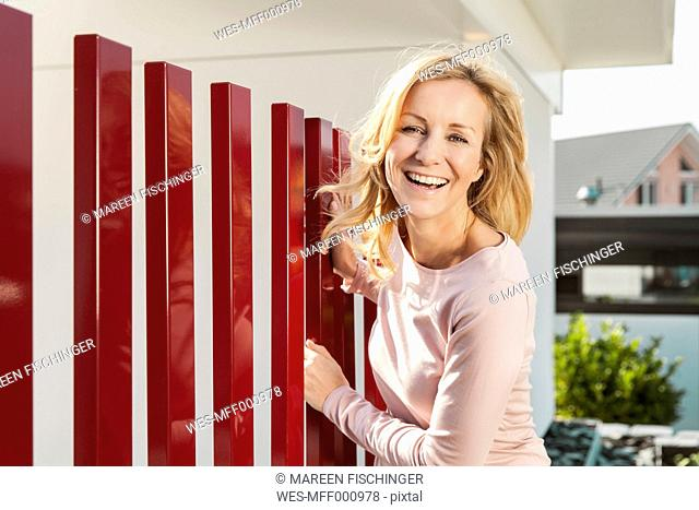 Smiling woman standing by red fence of residential house