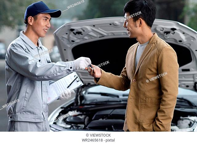 Young man talking with car mechanic