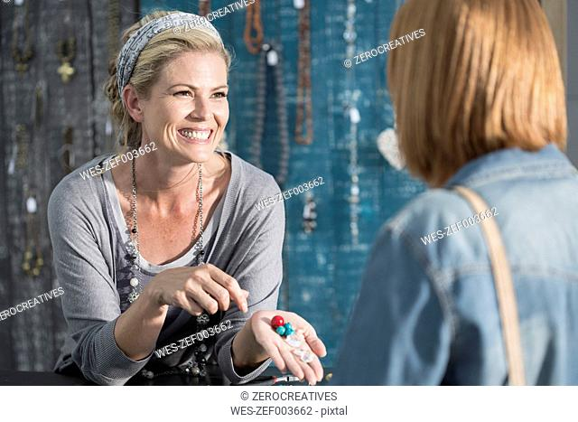 Woman showing beads to a customer