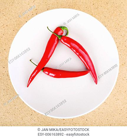 Fresh raw red hot chili peppers on plate arranged in A letter shape