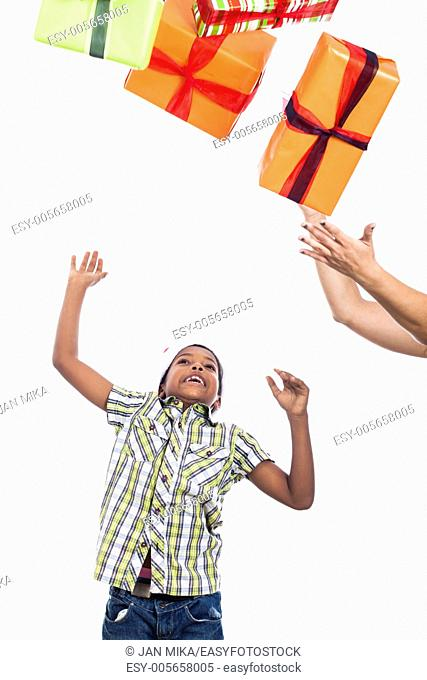 Exited child catching Christmas presents, isolated on white background