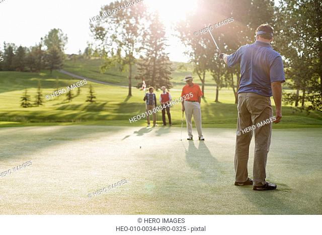 golfer lining up shot with putter