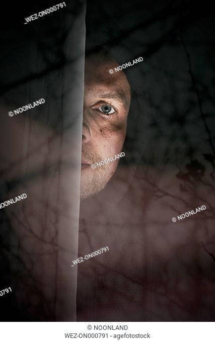 Man peeking from behind windowpane