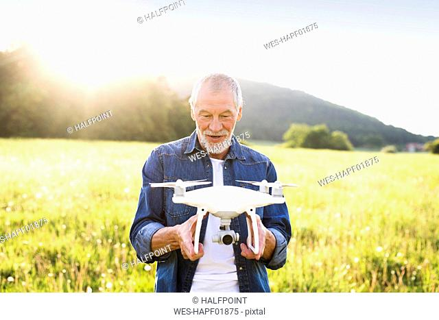 Portrait of senior man with drone on a meadow