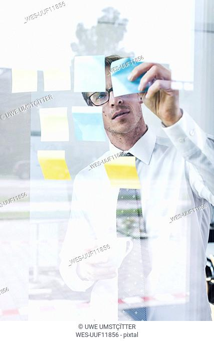 Businessman attaching adhesive notes at glass pane