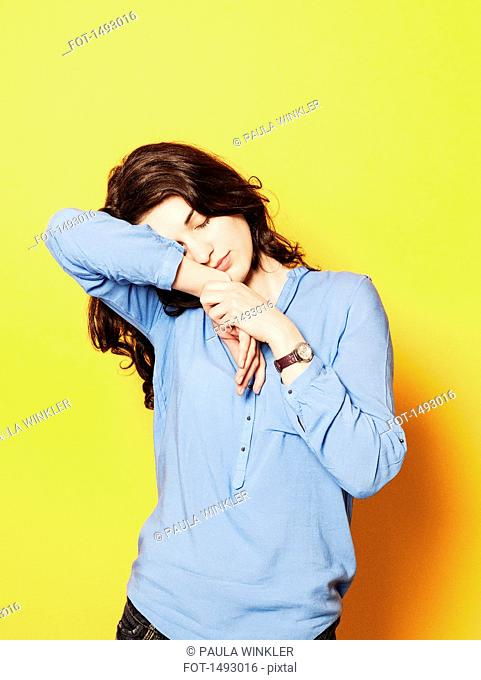 Tired young woman sleeping on hand against yellow background