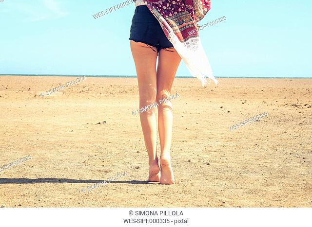 Spain, Tenerife, young woman walking in sand