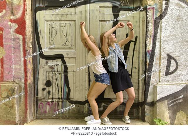 Two women dancing in door frame, graffiti, in Munich, Germany
