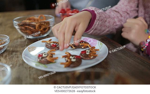 Many hands taking homemade sweets from the plate