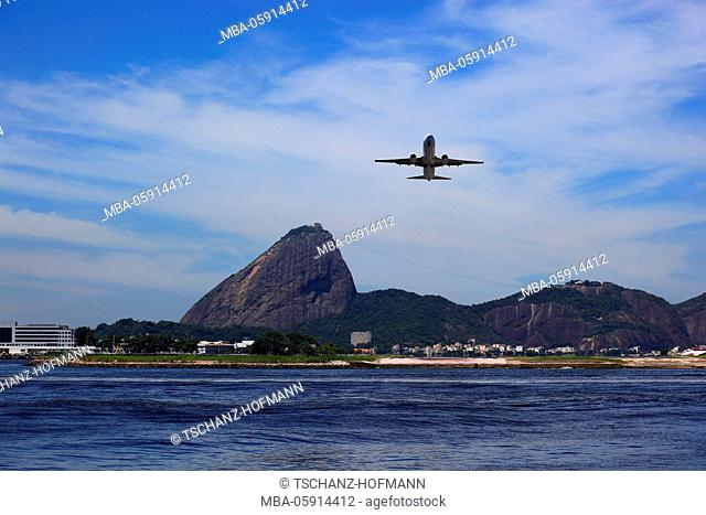 Airplane in the land approach to airport of Aeroporto Santos Dumont, Rio de Janeiro, Brazil. In the background the sugar loaf mountain