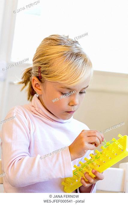 Little girl making bracelets with loomboard