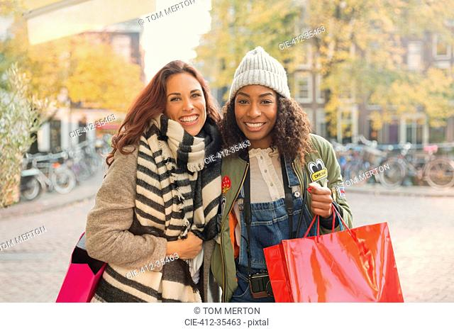 Portrait smiling young women with shopping bags on urban autumn street