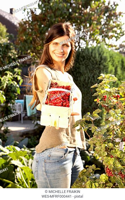 Smiling woman offering red currants in a basket