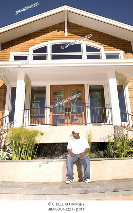 Man sitting in front of house