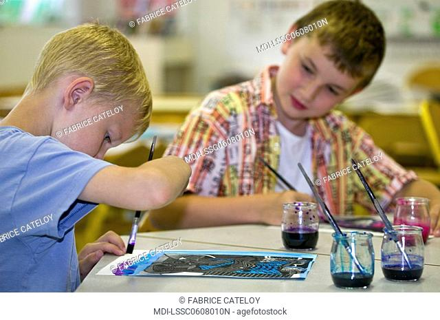 Two young boys painting in a school